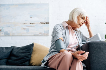 senior woman sitting on sofa and measuring blood pressure in apartment