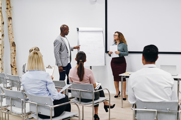Diverse coworkers discussing business concepts during a presenta