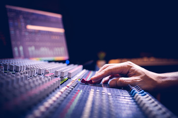 male producer, sound engineer hands working on audio mixing console in broadcasting, recording studio