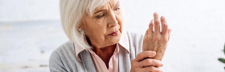panoramic shot of senior woman having pain in hand in apartment