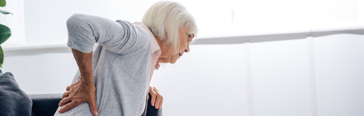 panoramic shot of senior woman having back pain in apartment
