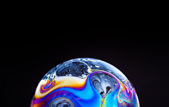close up of a colorful soap bubble isolated on a black background, looking like a planet in space.
