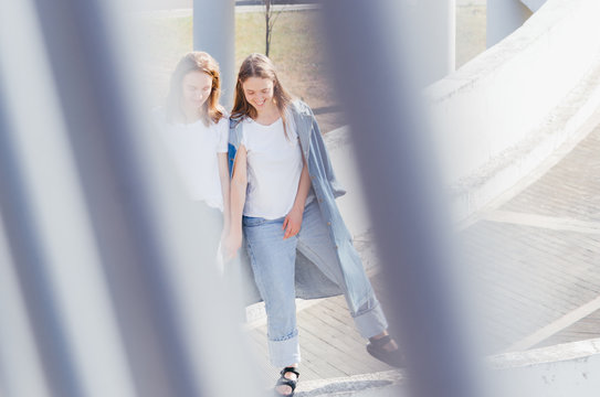 Two young women in white shirt and jeans talking and laughing together in parking