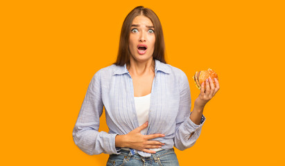Girl Holding Burger Having Stomachache Standing On Yellow Studio Background