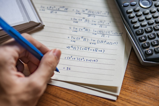 a left-handed person solving math problem
