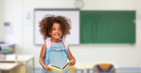 childhood, school and education concept - happy little african american girl with book and backpack over classroom background