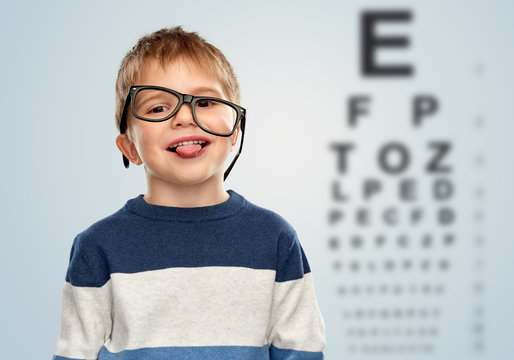 vision and children concept - portrait of smiling little boy with crookedly worn glasses showing tongue over eye test chart background