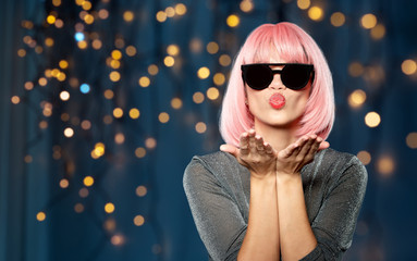 style, fashion and people concept - happy young woman in pink wig and black sunglasses sending air kiss to camera over festive lights on dark blue background