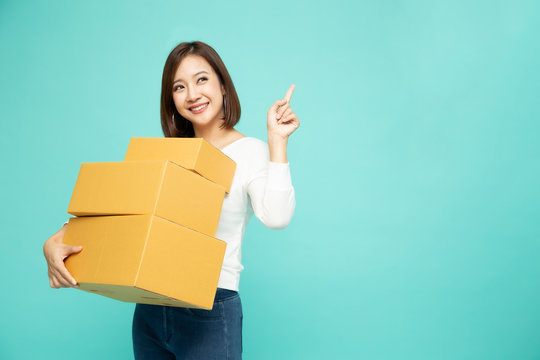 Happy Asian woman holding package parcel box and pointing finger to empty copy space isolated on light green background, Delivery courier and shipping service concept