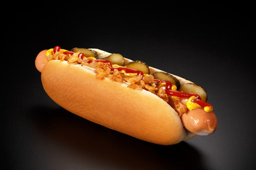 Danish hot dog with pickled cucumbers, fried onions, ketchup and mustard on a black background.