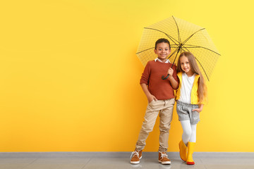 Fashionable little children in autumn clothes and with umbrella near color wall