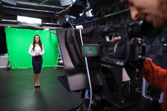 Presenter and video camera operator working in studio. News broadcasting