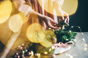 Girl making a handmade christmas wreath. Idea for the festive decoration of the interior. Christmas mood. Close up hand with christmas star.