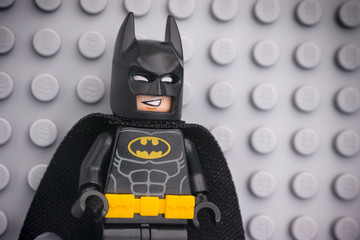 Tambov, Russian Federation - November 08, 2019 Portrait of Lego Batman minifigure standing against Lego gray baseplate background.