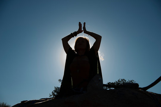 Silhouette of a priestess in ceremony outside with the dark blue sky behind her.