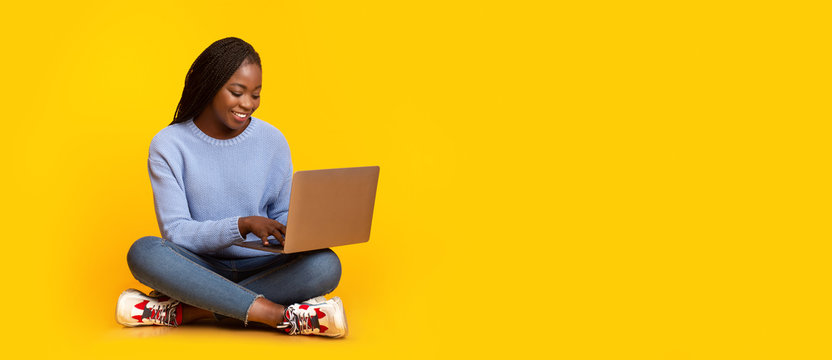 Smiling black girl using laptop over yellow background
