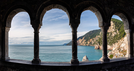 Poster de jardin Cote View of the Ligurian coast near Cinque Terre from the window of St. Peter's Church in Portovenere, Mediterranean coast through an arched stone window