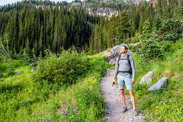 Man hiker standing with backpack on green alpine rocky meadow by pink fireweed wildflowers on trail to Ice lake near Silverton, Colorado in August 2019 summer Fotobehang