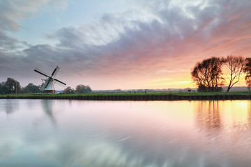 beautiful dramatic sunrise over windmill by river