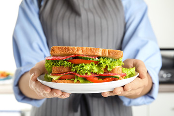 Woman holding plate with tasty sandwiches on light background, closeup