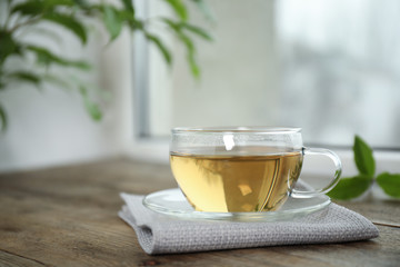Tasty hot green tea in cup on wooden table