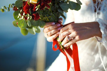 Beautiful bridal bouquet in bride's hands the background of sea and sun. Bride in an elegant white dress holds a stylish wedding bouquet with red and burgundy colors in her hands. Wedding day.