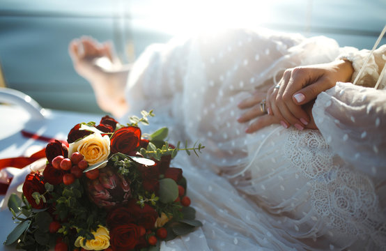 Beautiful stylish bride with wedding bouquet in the luxurious lace white dress on yacht board at sea. Elegant  engagement ring on the bride's finger. Wedding details. Wedding and marriage concept.
