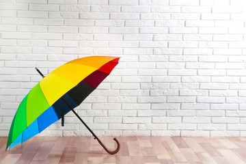 Wall Mural - Beautiful colorful umbrella near white brick wall. Space for text