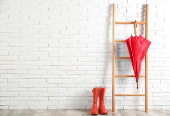 Wall Mural - Beautiful red umbrella on ladder and rubber boots near white brick wall. Space for text