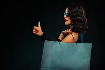 Black Friday sale concept for shop. Girl in sunglasses holding big bag isolated on dark background...