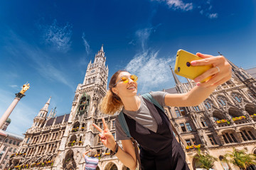 Cheerful Asian tourist girl takes a selfie on the background of Munich attractions to post photos on her blog and social networks