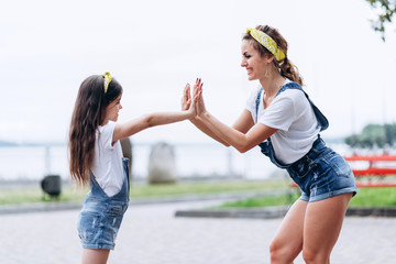 Mom and daughter are happily playing on the street and looking each other.- Image