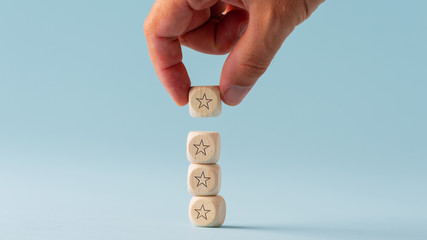 Fototapeta Male hand stacking five wooden dices with star shape on them obraz