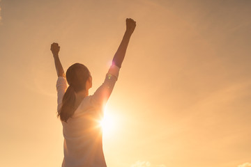 Strong young woman with arms up to the sky. People winning and victory concept. Wall mural