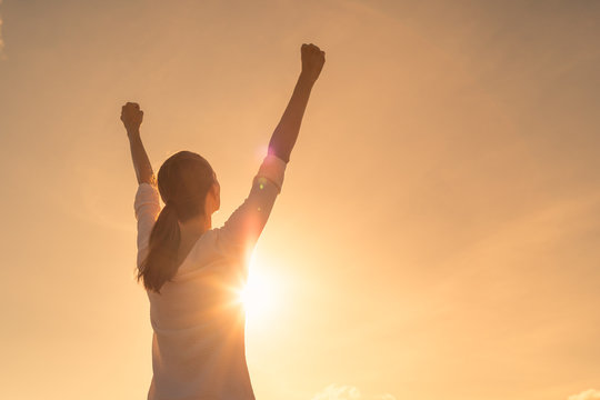 Strong young woman with arms up to the sky. People winning and victory concept.