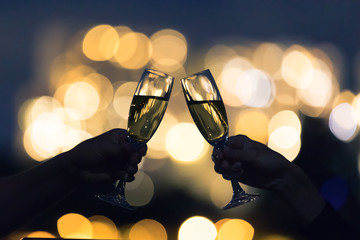 Cheers and celebration with champagne alcoholic drinks and beautiful golden city lights.