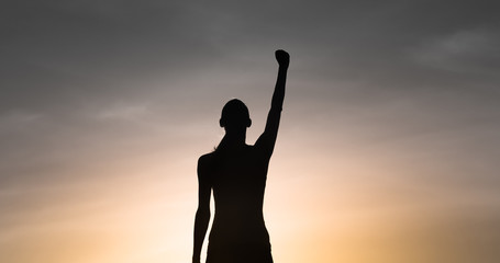 Strong determined female with hand raised to the sky. People  power concept.