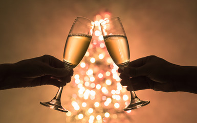 Two people enjoying champagne next to Christmas tree. Holiday celebration  concept.