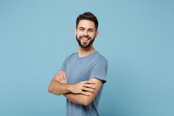 Young smiling cheerful handsome man in casual clothes posing isolated on blue wall background, studio portrait. People sincere emotions lifestyle concept. Mock up copy space. Holding hands crossed.