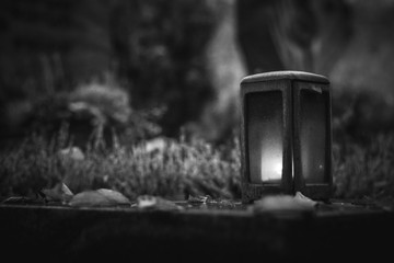 Vintage, retro photo of a lantern in an ancient cemetery. Grainy, noisy, artistic monochrome image. Halloween, all saints concept