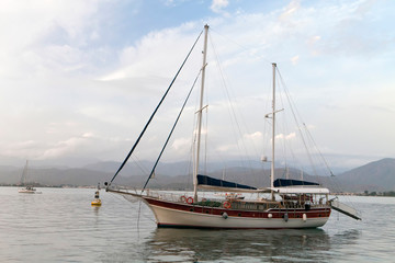Luxury yacht at mooring  in the harbor of Fethiye, Turkey, with mountains in rear