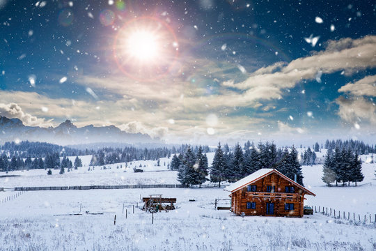 Fairy-tale winter landscape and cottage in woods at winter. Christmas concept.
