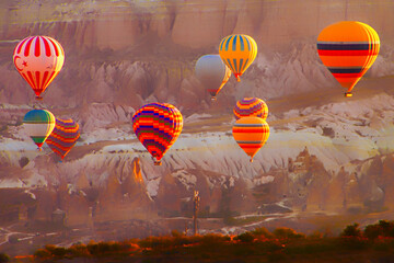 Multitude of colorful baloons ascending at dawn over Cappadocia, Turkey, with mountains in rear