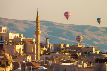 Baloons ascending at  sunrise over minaret and buildings of Cappadocia, Turkey, with mountaiins in background