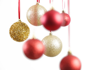 Gold and red Christmas shiny balls hanging in front of white background. Large glitter Christmas ornaments.