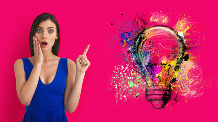 Wall Mural - Surprised woman pointing at big stylized light bulb on magenta background. Concept of idea and creativity