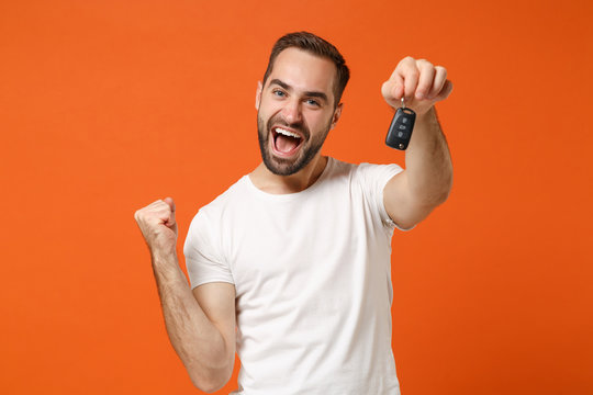 Joyful young man in casual white t-shirt posing isolated on orange background studio portrait. People sincere emotions lifestyle concept. Mock up copy space. Holding car keys, doing winner gesture.