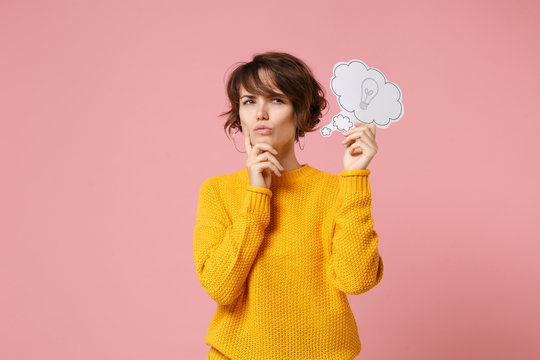 Pensive young brunette woman girl in yellow sweater posing isolated on pastel pink background. People lifestyle concept. Mock up copy space. Holding say cloud with lightbulb, put hand prop up on chin.