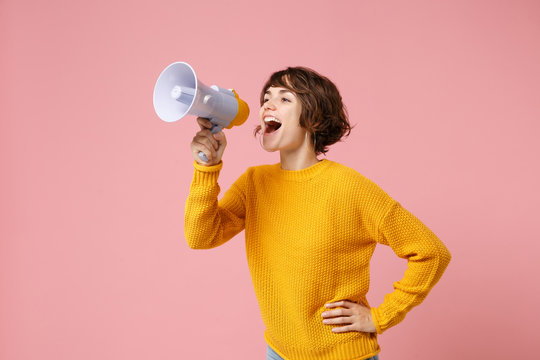 Funny young brunette woman girl in yellow sweater posing isolated on pastel pink wall background studio portrait. People sincere emotions lifestyle concept. Mock up copy space. Screaming in megaphone.