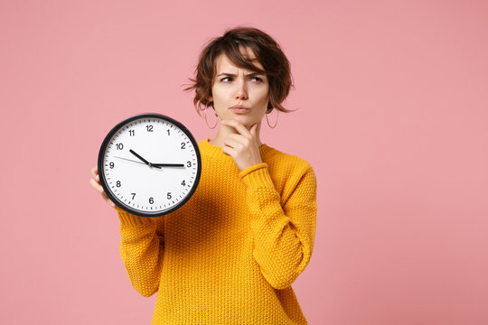 Pensive young brunette woman girl in yellow sweater posing isolated on pastel pink background, studio portrait. People lifestyle concept. Mock up copy space. Holding clock, put hand prop up on chin.
